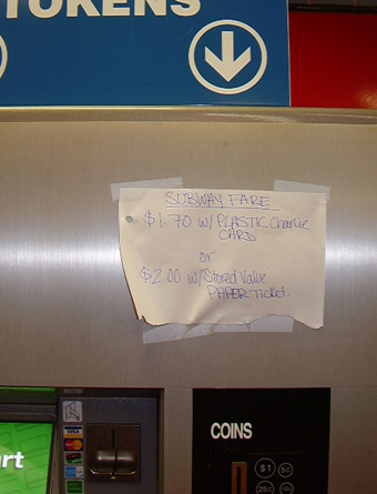 MBTA vending machine with handmade sign alerting users to fare increase
